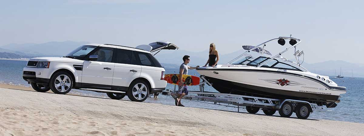 Range Rover Sport on beach towing a boat