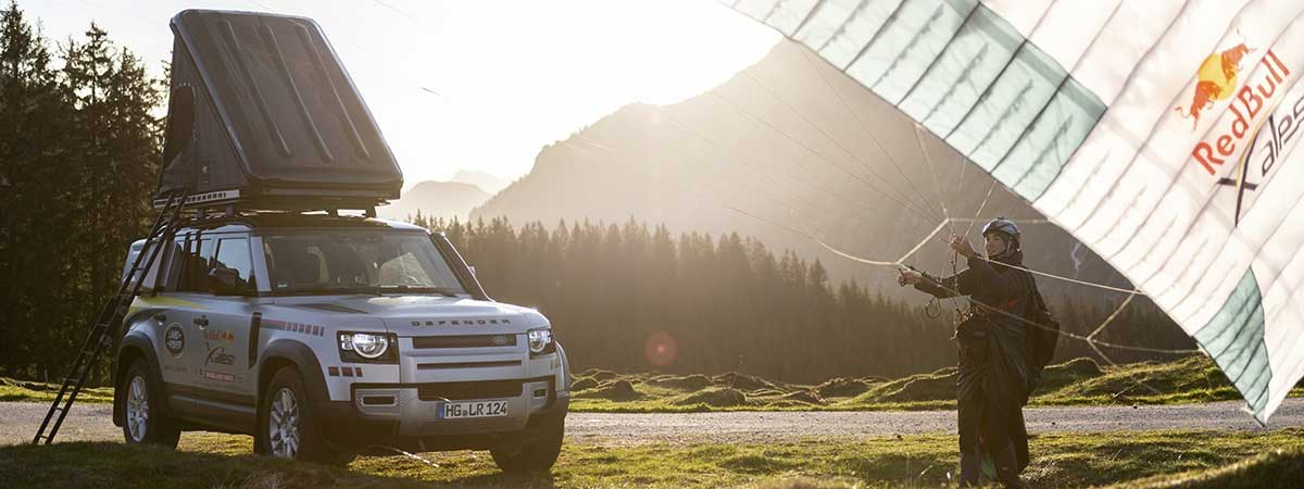Defender with a Red Bull x-alps adventure race competitor