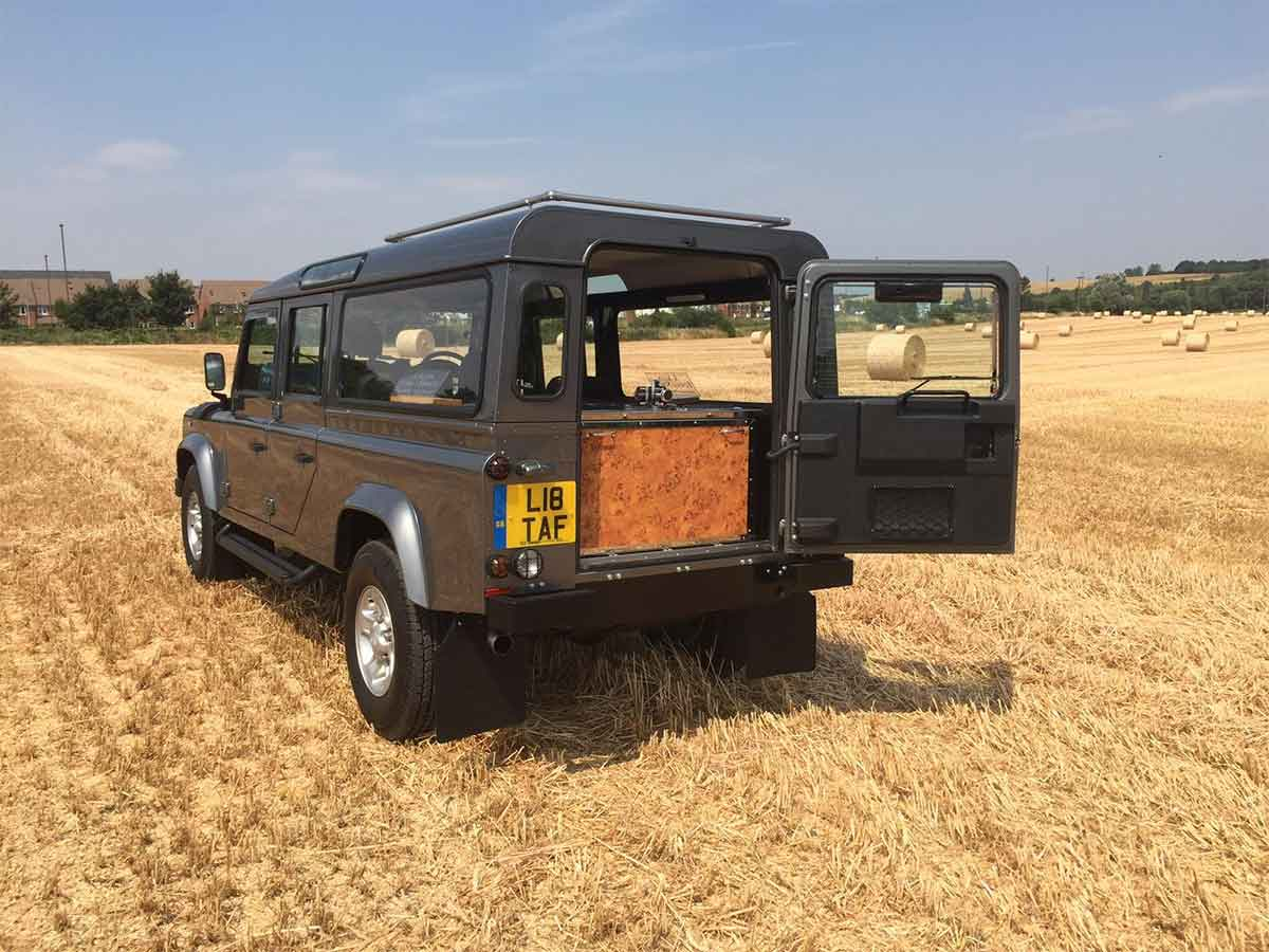 Defender Hearse in a field