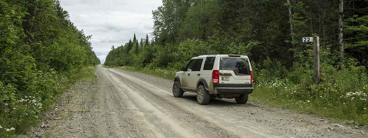 LR3 on a road in the Maine North Woods