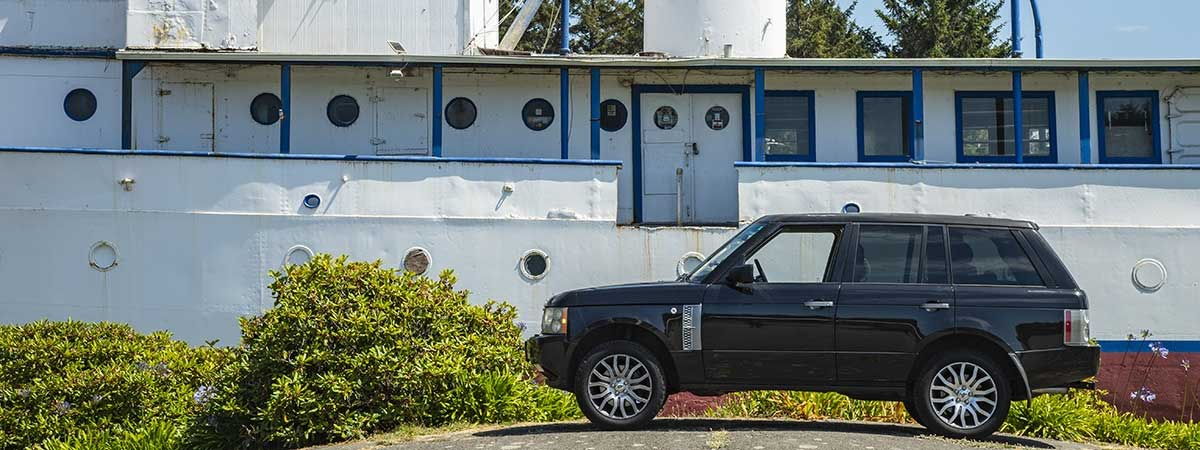 Range Rover with a beached yacht