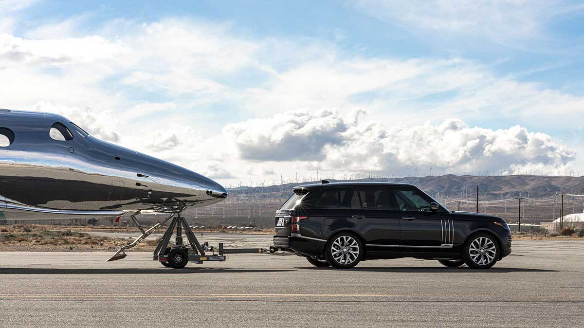 Land Rover showing strength by towing airplane - side photo